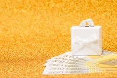 200-Euro - Scheine und Geschenkbox auf goldenem funkelndem Hintergrund Lizenzfreie Stockfotografie