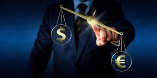 Euro segno che supera il dollaro in peso sulla scala dorata Fotografia Stock