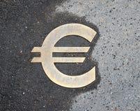 Euro sign on asphalt. Euro sign on wet asphalt Stock Photo