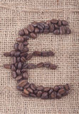 Euro sign in coffee beans. Euro sign of dark roasted coffee beans on jute Stock Photography