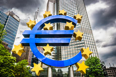 Euro sign at European Central Bank headquarters in Frankfurt, Germany. With dark dramatic clouds symbolizing a financial crisis Royalty Free Stock Photos