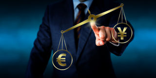 Euro Sign Outweighing The Yuan On A Golden Scale. Torso of a businessman operating a virtual golden scale on which the Euro sign is outweighing the China Yuan Stock Image