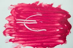 Euro sign painted on the textures of the sample smear lipstick.  Royalty Free Stock Photography