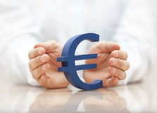 Euro sign protected by hands Stock Photo