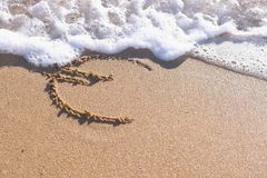 Euro sign written in the sea sand. Waves washed away the inscription. Euro sign written in the sea sand. Waves washed away the inscription stock image