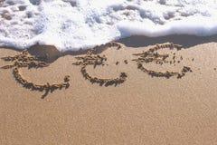 Euro signes écrits dans le sable de mer Les vagues ont enlevé l'inscription photos libres de droits