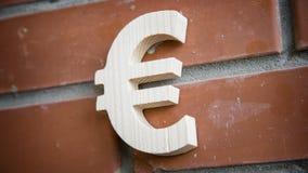 Euro simbolo di legno sul fondo del muro di mattoni Fotografie Stock