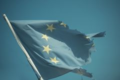 Euro skepticism concept. Torn EU flag wave on blue sky. European Union flag with twelve stars on sunny outdoor. Symbol. Of unity stock images