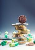 Euro soldi e medicinali Euro monete e pillole Monete impilate su a vicenda nelle posizioni differenti e liberamente in pillole in immagine stock