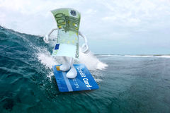 Euro surfing with credit card surfboard Stock Image