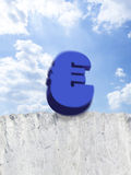 Euro symbol falling from edge of cliff Stock Photo