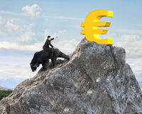 Euro symbol; gold; money; top; business man; riding; black; bear; market; bearish; rider; obedient; wild; animal; losing money; cl Stock Photography
