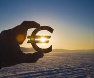 Euro symbol in hand on sunset background Royalty Free Stock Image