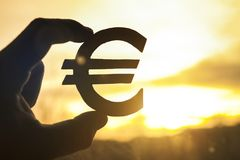 Euro symbol in hand on sunset background Royalty Free Stock Photo