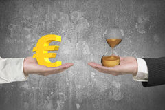 Euro symbol and hour glass with two hands Stock Photos