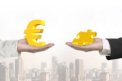 Euro symbol and puzzle piece with two hands Royalty Free Stock Photography