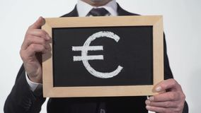Euro symbol rysujący na blackboard w biznesmen rękach, Europejska waluta, finanse zbiory