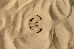 Euro Symbol Under the Sand. Euro Symbol or Sign Covered with Sand in the Sun after Crisis royalty free stock images