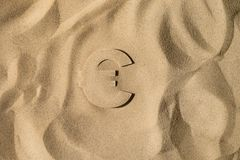 Euro Symbol Under the Sand. Euro Symbol or Sign Covered with Sand in the Sun after Crisis royalty free stock image