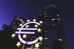 Euro tekenstandbeeld in franfurt met scyscrapers bij nacht royalty-vrije stock afbeelding