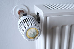 Euro thermostat on radiator. Euro coin on end of radiator thermostat valve with white wall in background Royalty Free Stock Photo