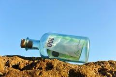 euro 100 in una bottiglia sulla spiaggia Fotografie Stock Libere da Diritti