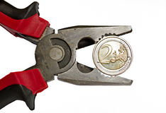 Euro under pressure. Pliers squeezing two euro coin Stock Photography
