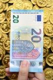 Euro venti a disposizione e monete di oro Fotografia Stock