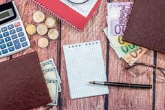 Euro vs dollar. With notepad, coin, pen on desk royalty free stock images