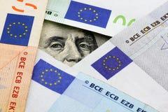Euro vs dollars. Franklin stare through space between euro banknotes Royalty Free Stock Photos