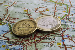 Euro vs Drahma. Euro coin and an old Greek coin drachma on a map Stock Photography