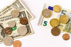 Euro vs us dollar. Two group of bills and coins of euros and dollars, lay over white, face opposing stock photography