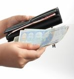 Euro and wallet. A hand holding a wallet and some euro bills stock photo