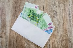 500, 100 euro  in a white envelope on a wooden background. View from above. 500, 100 euro  in a white envelope on a wooden background royalty free stock photography