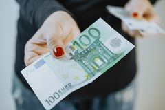 100 euro in Women`s hands and a wallet.  Royalty Free Stock Image