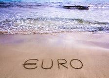Euro woord dat in het zand op een strand wordt geschreven royalty-vrije stock foto's