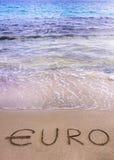 Euro woord dat in het zand op een strand wordt geschreven, dat door zeewater wordt gereinigd Stock Afbeeldingen