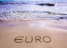 Euro word written in the sand on a beach. Currency concept Royalty Free Stock Photos