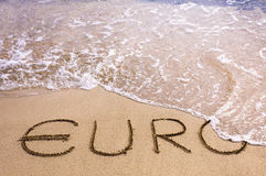 Euro word written in the sand on a beach, washed away by sea water. Instability concept Royalty Free Stock Photo
