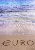 Euro word written in the sand on a beach, washed away by sea water Stock Images