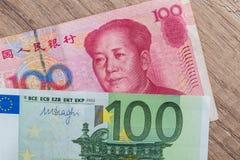 100 euro and 100 yaun bills. On desk Royalty Free Stock Photo