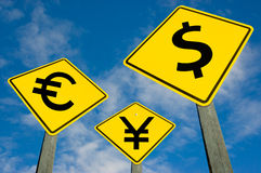 Euro, yen and dollar symbols on road sign. Euro, yen and dollar symbols on yellow traffic signs stock images