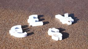 Euro, yen and dollar symbols on the sand. Stock Photos