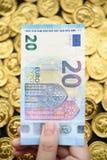 Euro zwanzig an Hand und Goldmünzen Lizenzfreies Stockbild
