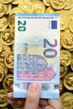 Euro zwanzig an Hand und Goldmünzen Stockfotografie