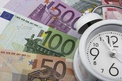 Euroanmärkningar och klocka äganderätt för home tangent för affärsidé som guld- ner skyen till Royaltyfria Foton