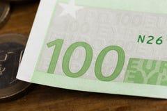 100 euroanmärkningar och mynt avbildar arkivfoto