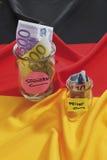 Euroanmerkungen im Behälter auf deutscher Flagge Lizenzfreies Stockfoto