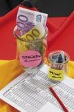 Euroanmerkungen im Behälter mit Dokument auf deutscher Flagge Lizenzfreie Stockfotos