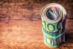 Euroanmerkungen mit Reflexion Fünf, 10 und fünfzig Eurobanknoten Fokus auf Seil Nahaufnahme von gerollte Eurobanknoten auf Beton  Stockfotografie